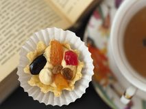 Cake with butter cream and fruit near a cup of tea at the opened book. A tasty dessert in the pleasant company a tea drinking and an entertainment. Close up stock photography