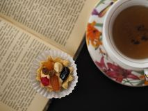 Cake with butter cream and fruit near a cup of tea at the opened book. A tasty dessert in the pleasant company a tea drinking and an entertainment royalty free stock image