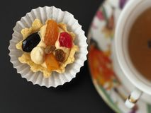 Cake with butter cream and fruit near a cup of tea. A tasty dessert in the pleasant company a tea drinking and an entertainment stock images