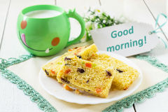 Cake with candied fruit, milk in a mug Stock Photos
