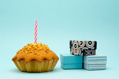 Cake with a candle and a box with a gift on a blue background Stock Images