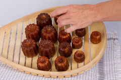 Cake canneles from France. Cakes canneles, specialties of Bordeaux, France, with a woman's hand royalty free stock photo