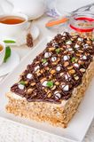 Cake with caramel cream, meringue, peanuts and chocolate glaze. On a white wooden background royalty free stock image