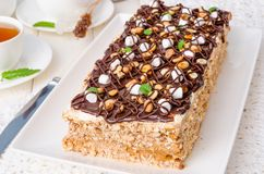 Cake with caramel cream, meringue, peanuts and chocolate glaze. On a white wooden background stock images