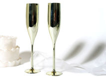 Cake and Champagne. White cake, gold champagne flutes and white ribbon stock photo