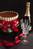 Cake and champagne. Tiramisu cake with red ribbon on a silver stand, champagne and crystal glasses on a black background stock image