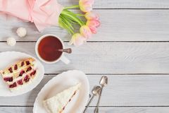 A cake with cherries, cup of tea and pink tulips on white wooden table Stock Photography