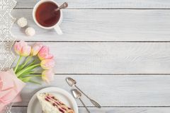 A cake with cherries, cup of tea and pink tulips on white wooden Royalty Free Stock Image