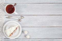 A cake with cherries and a cup of tea on white wooden table Stock Photo