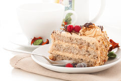 Cake with cherries and nuts. A piece of sponge cake decorated with cherries and walnuts placed on a plate with a spoon against the mug of tea Royalty Free Stock Images