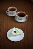 Cake with cherry and a cup of tea Stock Photo
