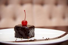 Cake with cherry on a white plate royalty free stock photo