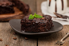 Cake chocolate brownies with dark chocolate dressing and mint. On wooden table royalty free stock photo