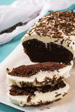 Cake with chocolate and dark beer. Icing cream cheese and sprinkled with chocolate on turquoise wooden background Stock Photography
