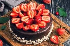 Cake in chocolate icing decorated with fresh strawberries. Selective focus. Rustic style. royalty free stock images