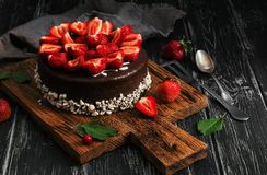 Cake in chocolate icing with fresh strawberries on a black rustic table board. Selective focus stock photos