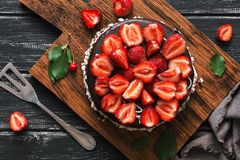 Cake in chocolate icing with fresh strawberries .Overhead, top view, flat lay. stock photos