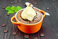 Cake with chocolate and pear in red bowl on dark board Stock Photo