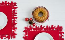 Cake with christmas decoration on red tablecloth and white wooden background. Cenital plane. Christmas cake with decoration on white wood background and red stock photography
