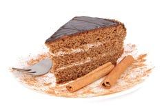 Cake and cinnamon. Slice of chocolate cream cake with cinnamon Royalty Free Stock Images