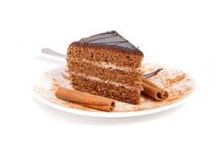 Cake and cinnamon. Slice of chocolate cream cake with cinnamon Royalty Free Stock Photography