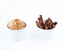 Cake and cinnamon sticks in white cups. On white background Stock Photography
