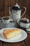 Cake with coconut flakes and coffee in the cup and the coffee pot Royalty Free Stock Photos