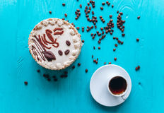 Cake, coffee beans and coffee on blue background Stock Photos