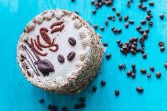 Cake, coffee beans and coffee on blue background Royalty Free Stock Photo