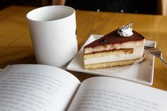 Cake, coffee and book. On the wooden table Stock Images
