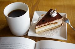 Cake, coffee and book. On the wooden table Stock Image