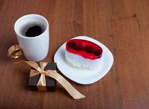 Cake and coffee with a small gift on a wooden background. Valentine`s Day.  royalty free stock photo
