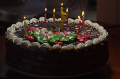Cake with colorful burning candles in dark Stock Photos