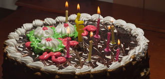 Cake with colorful burning candles in dark Royalty Free Stock Photography