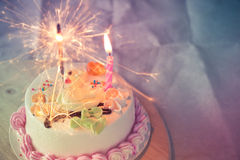 Cake with colorful sprinkles and a sparkler Stock Photo