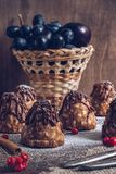 A cake with condensed milk and chocolate on a wooden table, in the background a basket with black grapes. Selective focus royalty free stock images