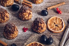 A cake with condensed milk and chocolate on a wooden table is decorated with berries and dried oranges. Selective focus.  stock photography