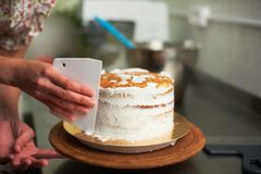 Cake cooking process. Spreading cream cake. kitchen and tools in the background Royalty Free Stock Images
