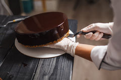 Cake covered in chocolate. Preparing round glaze cake covered in chocolate Stock Photo