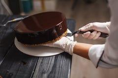 Cake covered in chocolate. Preparing round glaze cake covered in chocolate stock photo