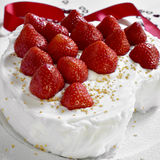 Cake covered with cream and topped with strawberries Stock Images