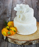 Cake covered with white fondant and buttercups. Royalty Free Stock Photos