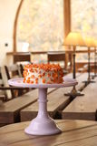 Cake covered in white rolled fondant and decorated with marzipan flowers on a stand.  royalty free stock photos