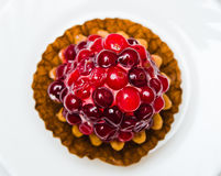 Cake with a cranberry on a white plate Royalty Free Stock Image