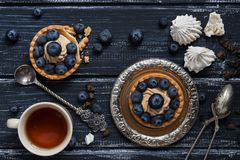 Cake with cream and blueberries on a rustic background. Vintage old utensils. Tea strainer and tea in a cup. Top on top. stock photography