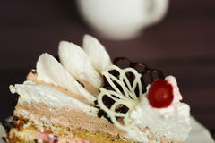 Cake with cream and cherry on a dark background Royalty Free Stock Photography