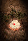 Cake with cream and a fir branch on a wooden background 1 Stock Photography