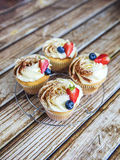 Cake with cream and sprinkled with cocoa, and strawberries and blueberries royalty free stock photos