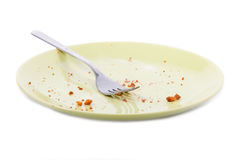 Cake crumbs and fork on yellow plate stock image