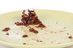 Cake crumbs leftovers on green plate on white Stock Photos